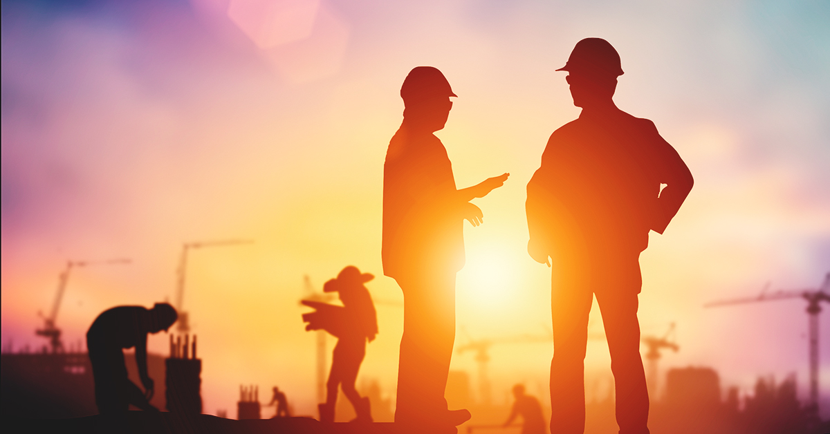 2 workers in a construction setting at sunset